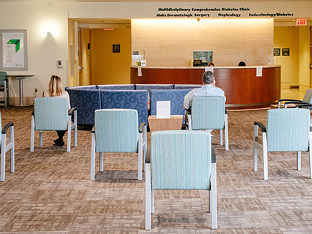 Back, two patients are sitting in chairs spread apart for COVID-19 (Coronavirus Disease) social distancing in the waiting area of a medical office in the Kirklin Clinic, May 2020.a