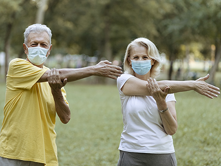 Joyful Senior Couple in Sportswear Stretching Outdoors in a Park on a Beautiful Spring Day While Wearing Face Protective Masks During Coronavirus Outbreak Living Active Healthy Lifestyle on COVID 19 Period