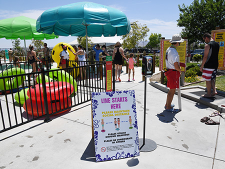 HENDERSON, NEVADA - MAY 30:  A sign asking guests to practice social distancing is posted at the entrance to a slide at Cowabunga Bay Water Park, which was allowed to open for the first time this weekend because of the coronavirus (COVID-19) pandemic on May 30, 2020 in Henderson, Nevada. The park would have opened on March 21 but had to wait until Nevada's Phase Two reopening of the economy, which includes operating at 50% capacity, new social distancing guidelines and other restrictions in place. As a thank you for waiting for the reopening, the park is only allowing season pass holders in on opening weekend; it opens to the public on June 1.  (Photo by Ethan Miller/Getty Images)
