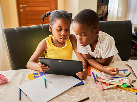 Cropped shot of two young siblings using a digital tablet while sitting at home