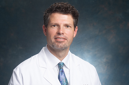 Head shot of Dr. Erik Hess, MD (Professor/Vice Chair for Research, Emergency Medicine) in white medical coat, 2018.