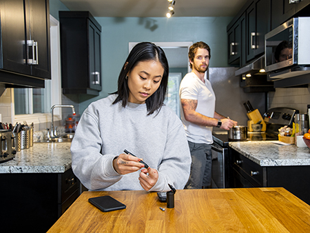 A young woman of Asian descent with diabetes holding a blood sugar monitor while her partner looks on.