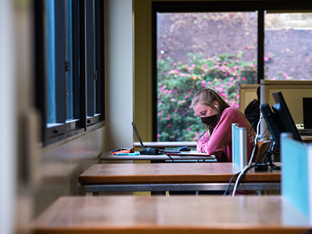 Student with mask on looking at laptop in a library.