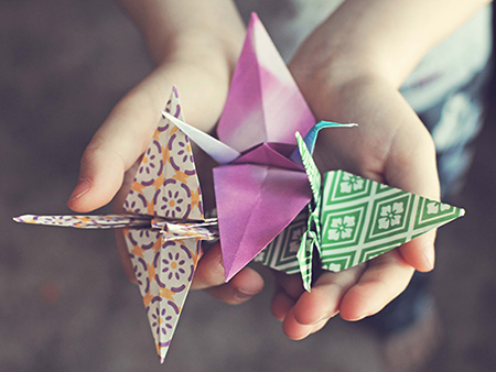 Boy holding three hand made origami cranes for Japan relief effort.