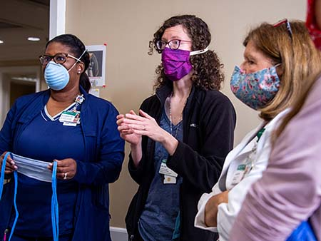 Alvernita McKinney, RN (Infection Prevention Manager, Infection Prevention and Control), Dr. Rachael Lee, MD (Assistant Professor, Infectious Diseases), and another woman, all wearing PPE (Personal Protective Equipment) face masks while at a demonstraton testing the fit of PPE gear at the UAB Hospital COVID-19 (Coronavirus Disease) Command Center in the North Pavilion on April 7, 2020.
