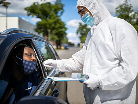 Doctor in a protective suit taking a nasal swab from a person to test for possible corona virus infection on the street. Diver through covid-19 testing center in city.