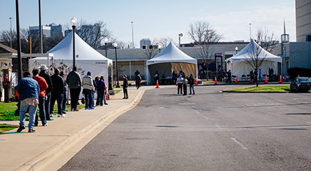 Overall of people standing in line near white tents at the UAB COVID-19 Vaccination Site at Parker High School on February 10, 2021.