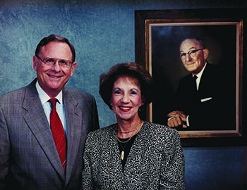 Charles and Patsy Collat with a portrait of Mayer Electric Founder Ben Weil, Patsy's father