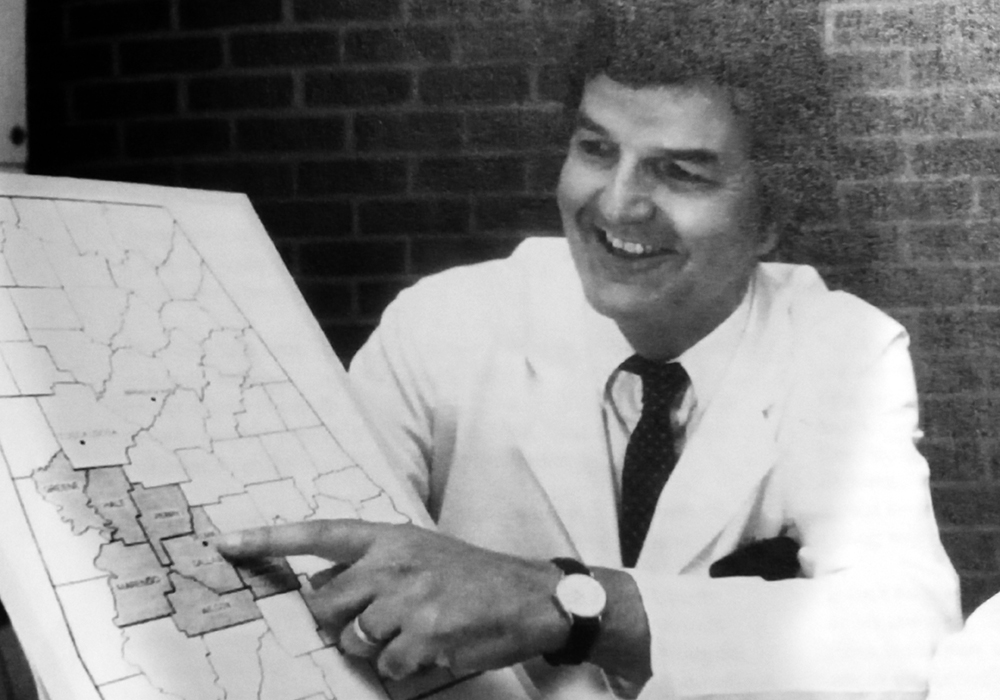 In this vintage photo, Edward Partridge, M.D., reviews a map of Alabama and the target areas for the Office of Community Outreach & Engagement.