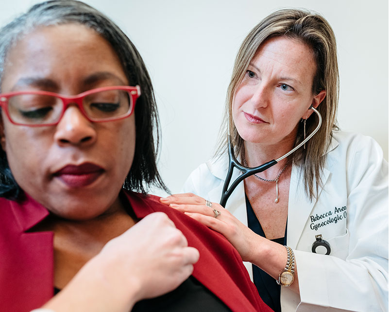 Physician using stethoscope to listen to patients breathing.
