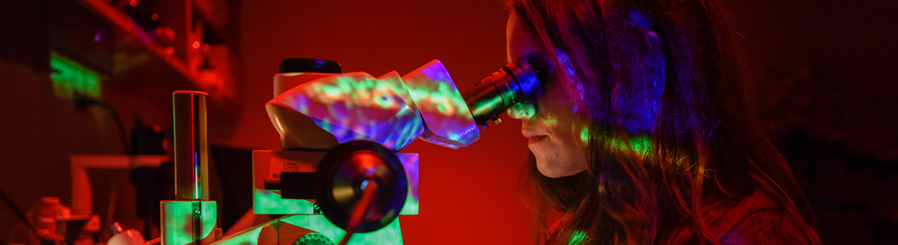 UAB Optometry student looking through microscope.