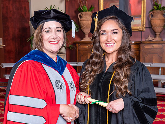 Hannah Greenfield, left, and School of Optometry Dean Nichols at graduation.