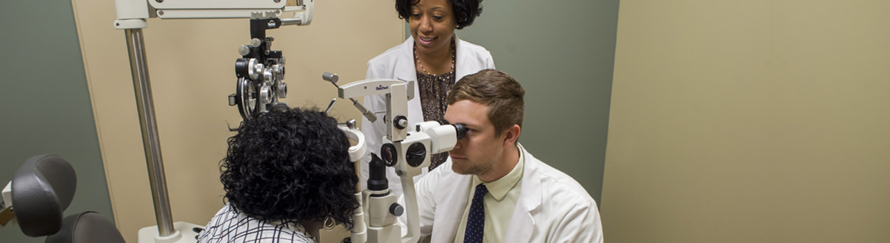 UAB Optometry student looking through optometry equipment at patient's eye. UAB Optometry faculty member standing behind student overseeing exam.