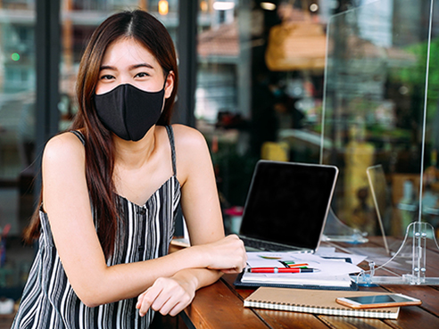 Young 20s Asian woman looking at camera while wearing a protective mask with laptop, mobile phone, and notebook for working outside in casual dress. Corona Virus - Covid 19 work online concept.