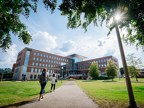 Wide shot of students walking on sidewalk in front of University Hall, 2019.