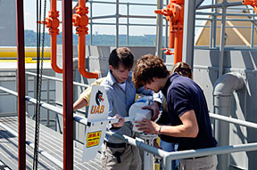 Senior engineering design students Kevin Nord (left) and Chris Yancey mount the wind turbine their team designed and constructed on a retractable pole atop the 18-story Alabama Power headquarters building.
