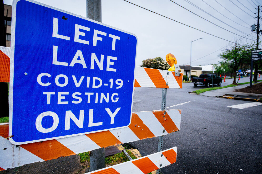 "A blue street sign that reads ""Left Lane Covid-19 Testing Only"" near the Birmingham downtown COVID-19 testing site."