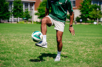 Close-up, legs of male student kicking a soccer ball on the Campus Green, June 2019.
