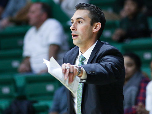 Robert Ehsan coaches on the sidelines of a men's basketball game as associate head coach. (Photo from UAB Sports)