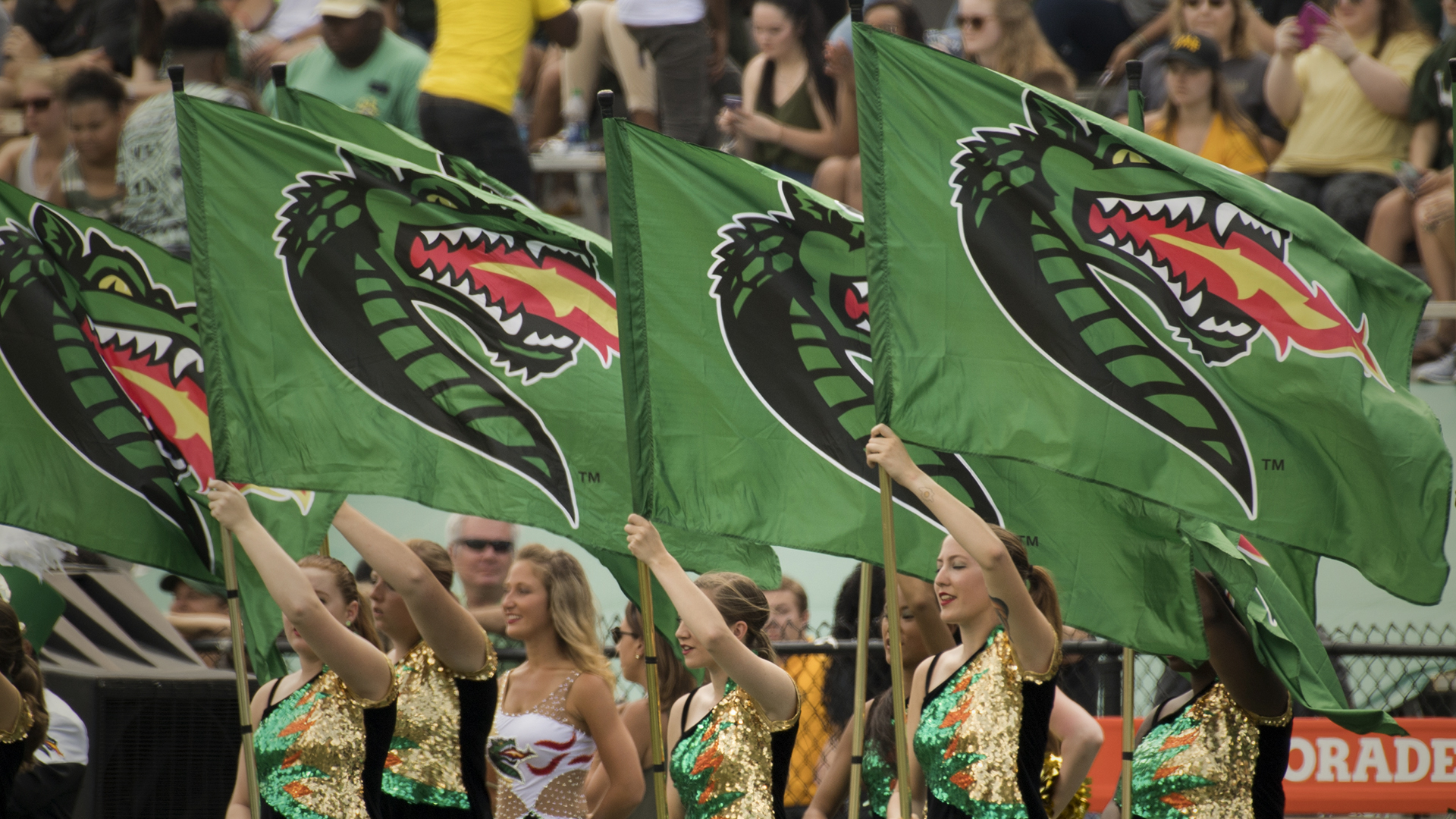 Colorguard holding UAB flags at football game with crowd in the background.