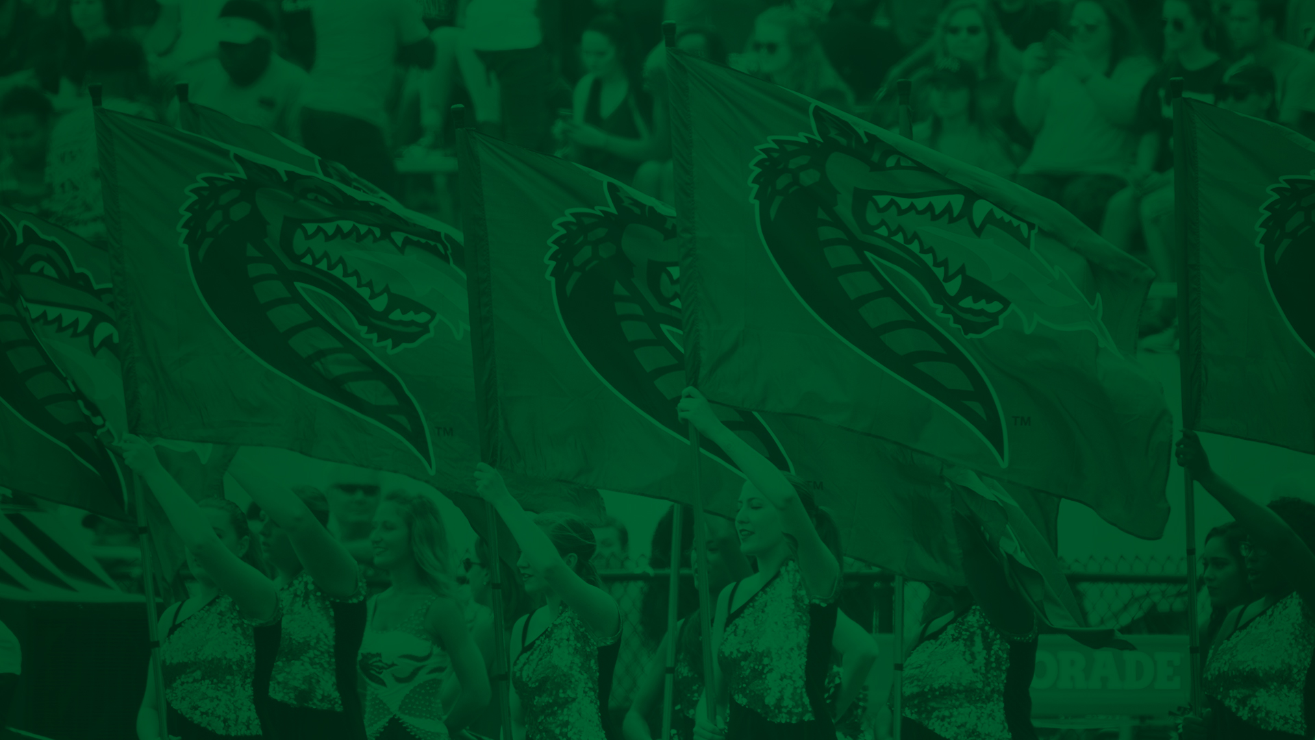 Colorguard holding UAB flags at football game with green overlay.