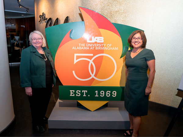 UAB 50th logo with two UAB staff posing next to it.