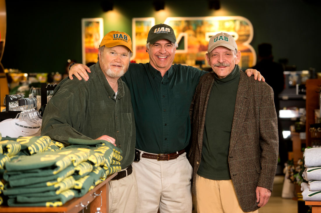 Photo of alumni Tommy Burns, Richard Dewberry, and Chuck Snow wearing UAB clothing at UAB Bookstore