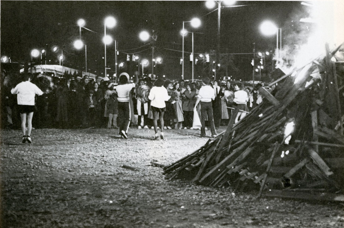 Photo of bonfire and cheerleaders with students