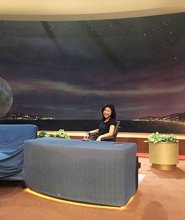 Photo of Lim at desk on the Conan set