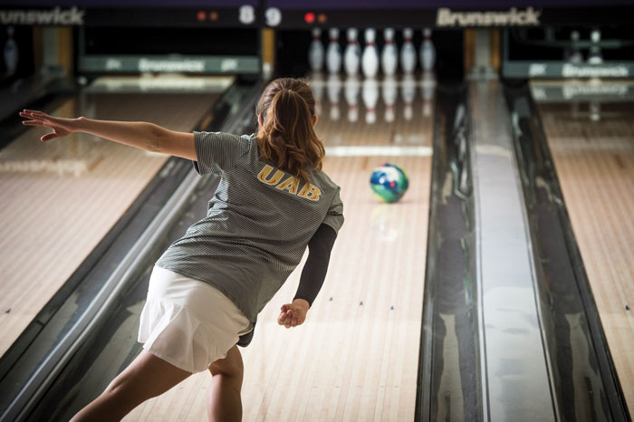 Photo of UAB bowling athlete with ball rolling toward pins