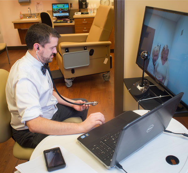 Eric Wallace examines a patient using telehealth technology