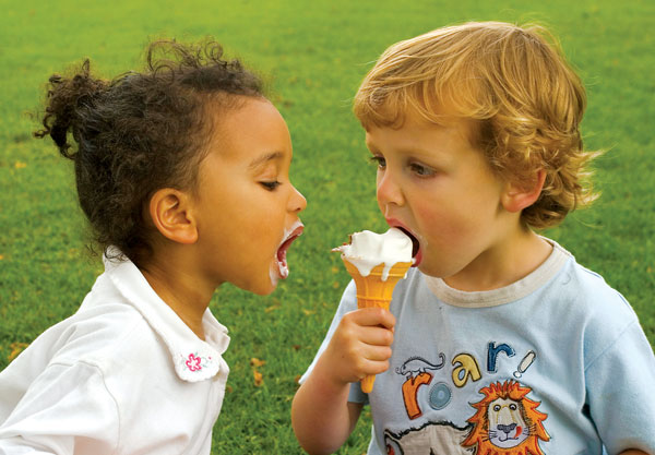 Photo of two children sharing an ice cream cone