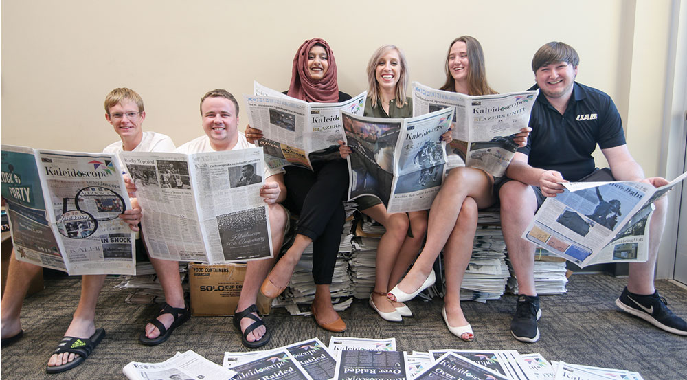 Photo of 2017-2018 Kaleidoscope staff looking at newspapers and sitting on newspaper stacks