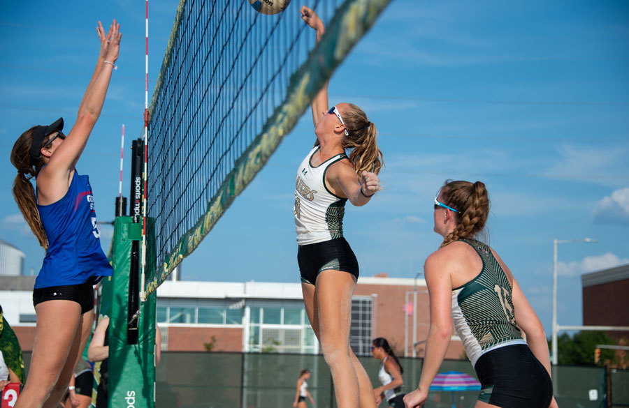Action photo from beach volleyball match, with players on both sides of the net leaping for the ball
