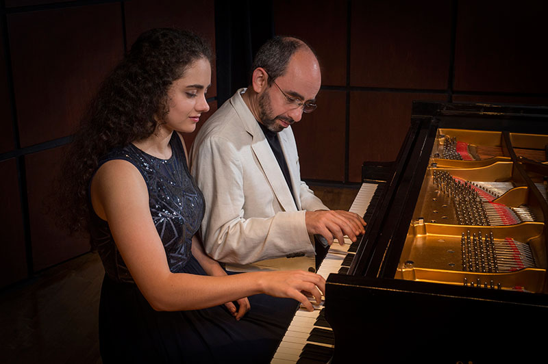 Photo of Sasha and Yakov Kasman performing together on piano