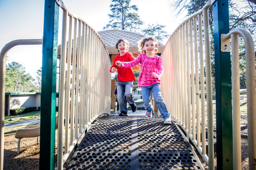 Photo of little boy and little girl on playground bridge