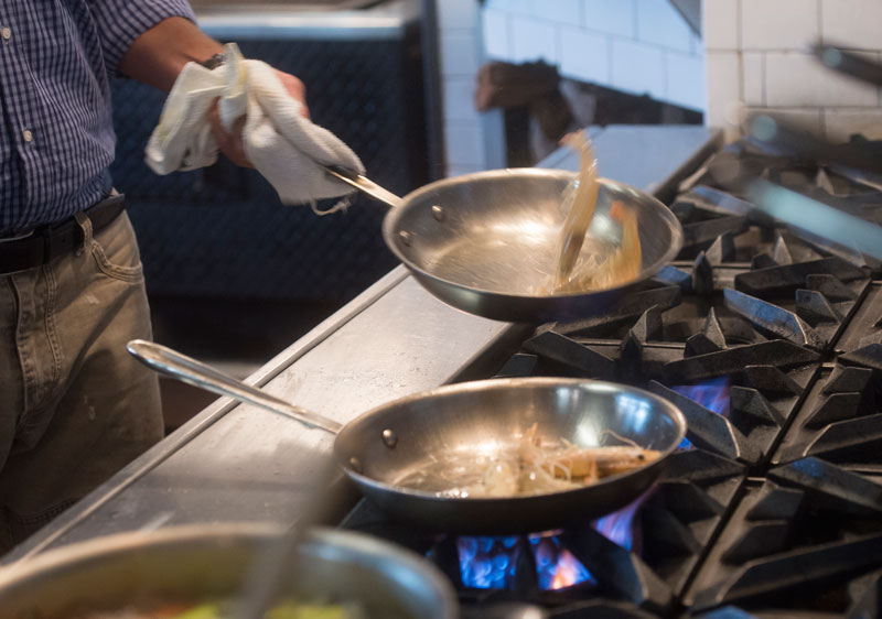 Photo of Hastings cooking shrimp in pan on stovetop