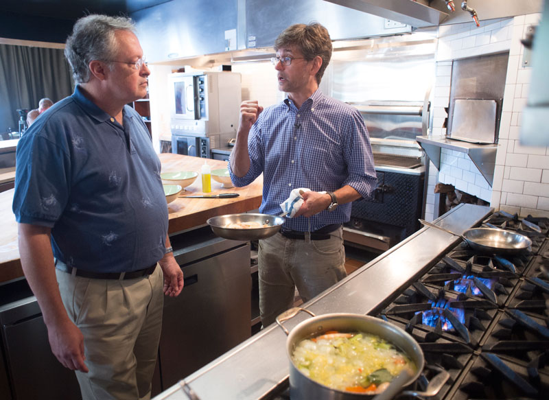 Photo of Stephen Watts and Chris Hastings discussing shrimp in kitchen
