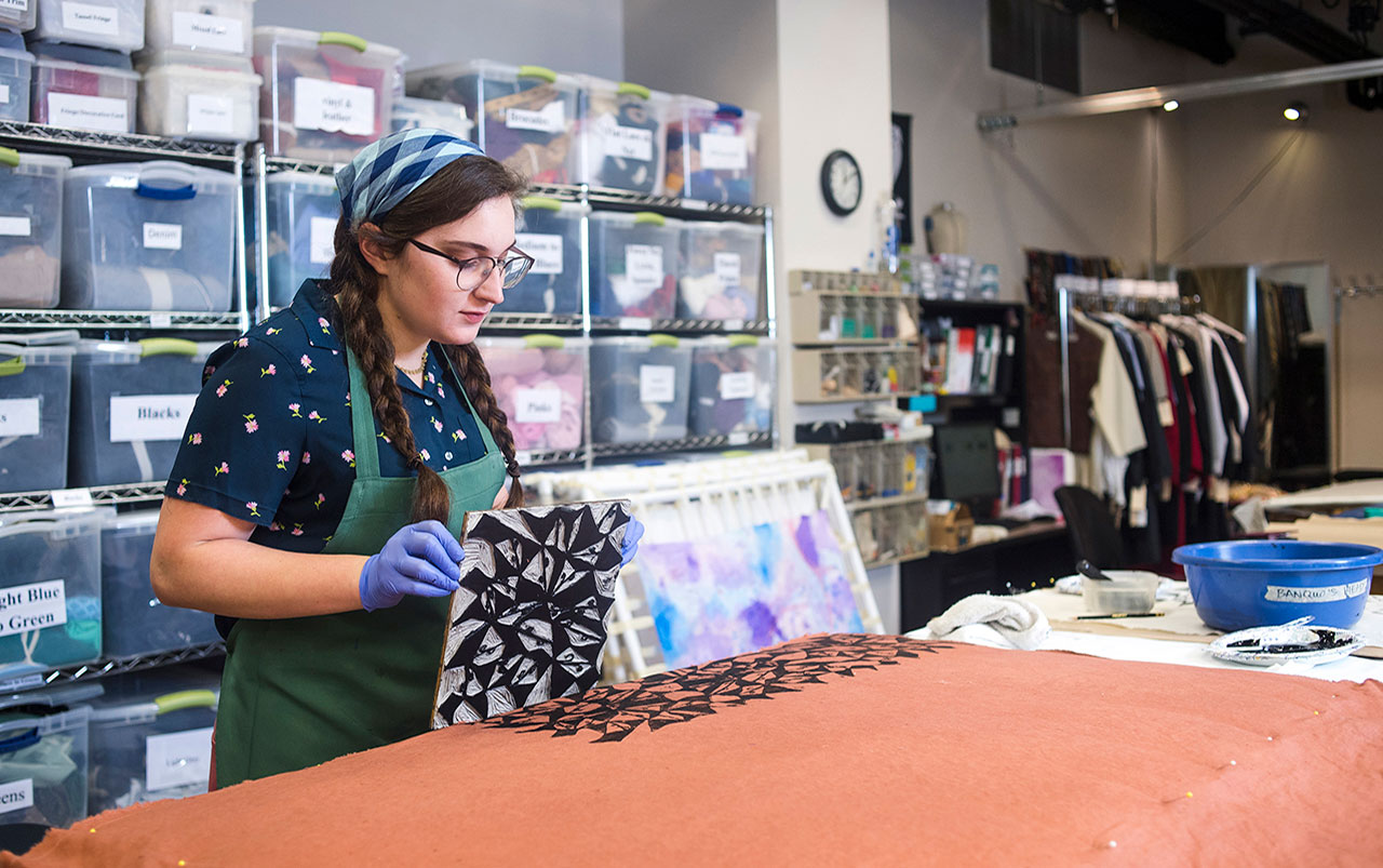 Photo of student block-printing textile in UAB Costume Shop