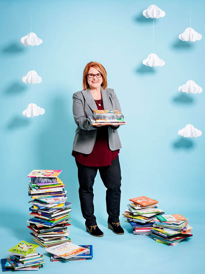 Photo of Jennifer Summerlin surrounded by stacks of books in front of blue background with paper clouds