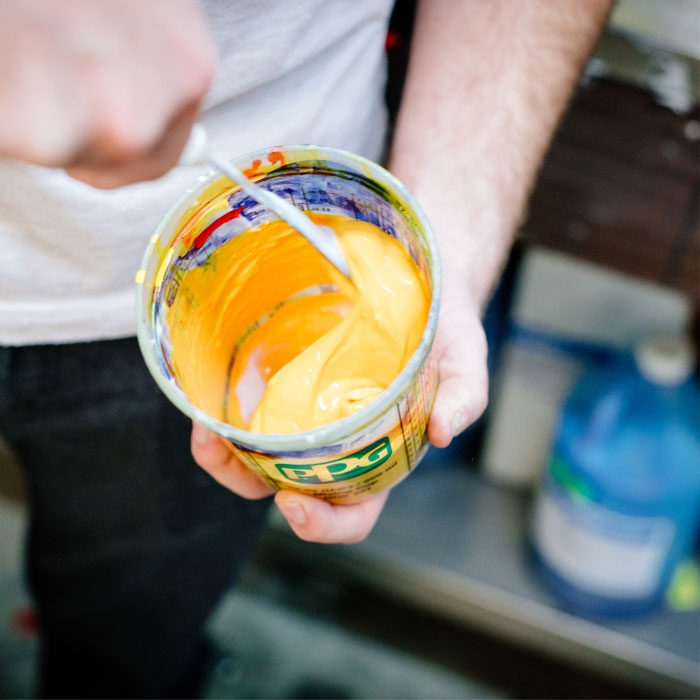 Closeup photo of Brett Forsyth mixing yellow ink
