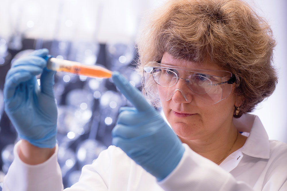Photo of Eugenia Kharlampieva in lab looking at orange solution in tube
