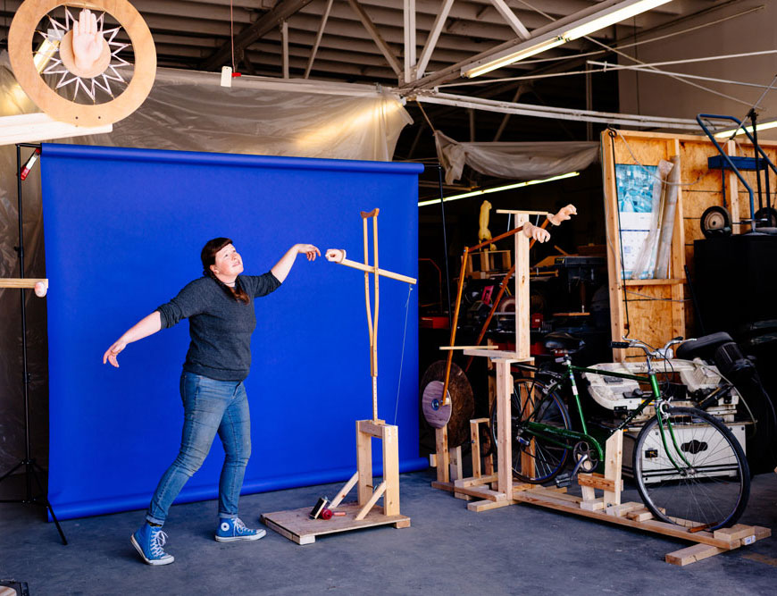 Photo of Stacey Holloway in garage recreating Adam and God image from Sistine Chapel with one of her sculptures