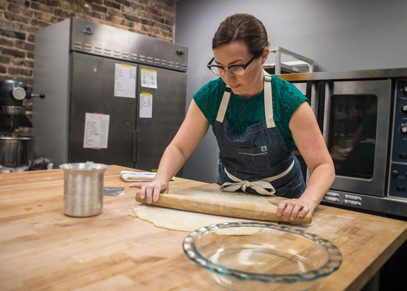 Photo of Kristen Farmer Hall rolling out dough in Feast & Forest kitchen