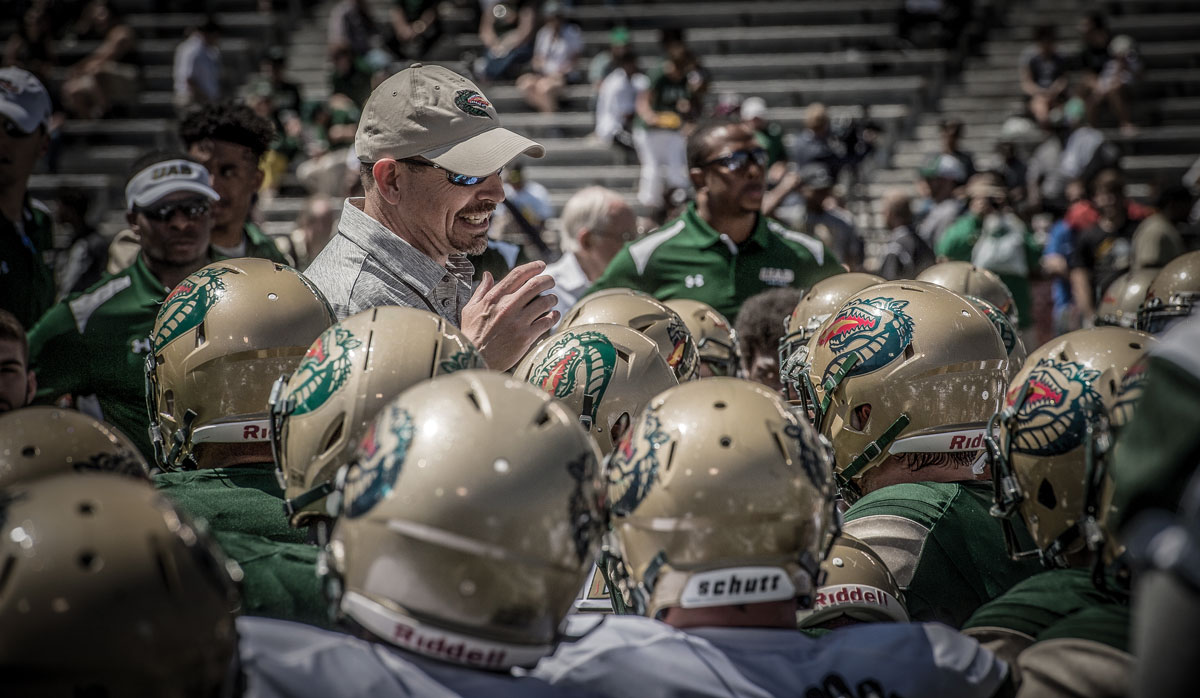 Photo of Coach Clark surrounded by players at the 2017 Spring Game