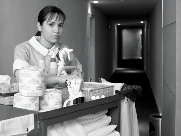 Photo of housekeeper with cart in hotel hallway