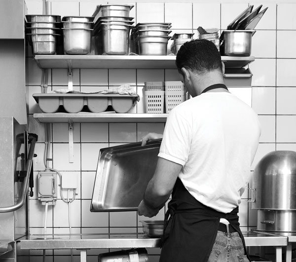 Photo of man washing dishes in restaurant