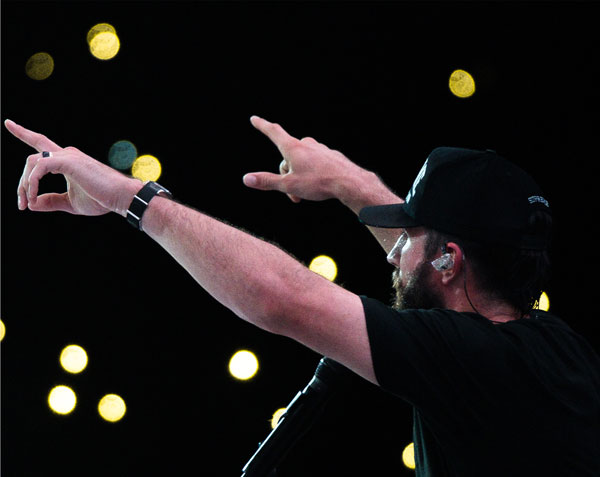 Photo of Sam Hunt performing with lights in background