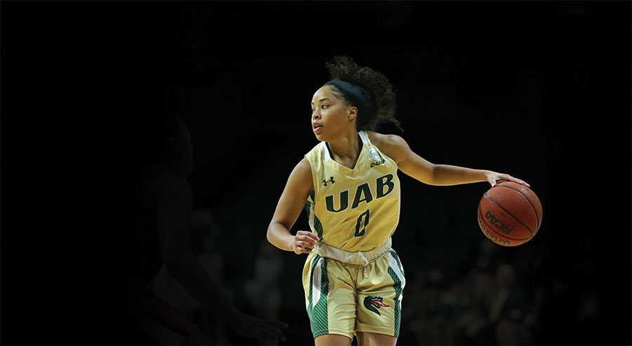 Photo of player Miyah Barnes dribbling the ball during a Bartow Arena game