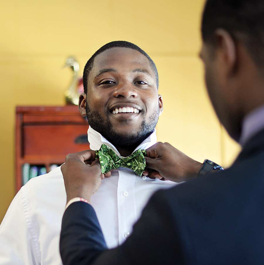 Photo of Booker Taylor III smiling while Tavaris Handley adjusts his green bow tie